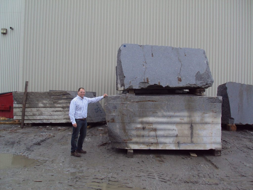 Luc Collette standing with quarried granite blocks